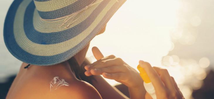 Sunbathing woman applying sunscreen.