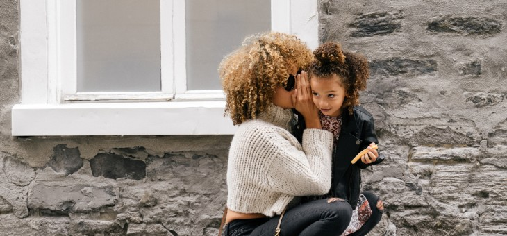 Cheers to Moms and Women- Mom whispering to her little girls ear.