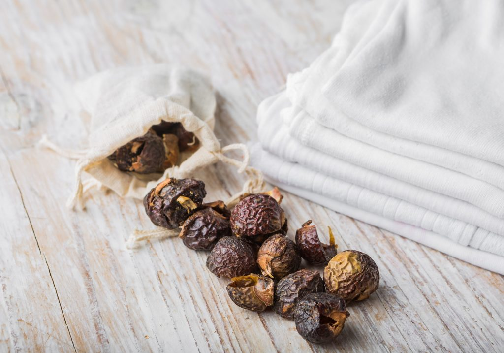 Nutshells of soapnuts in a cotton bag for laundry on a white wood.