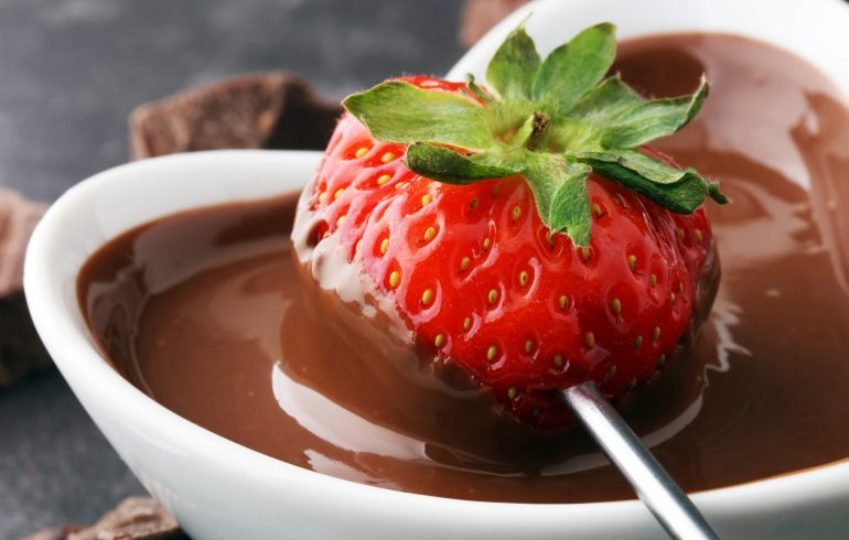 Fondue with melting chocolate or melted chocolate and strawberry.