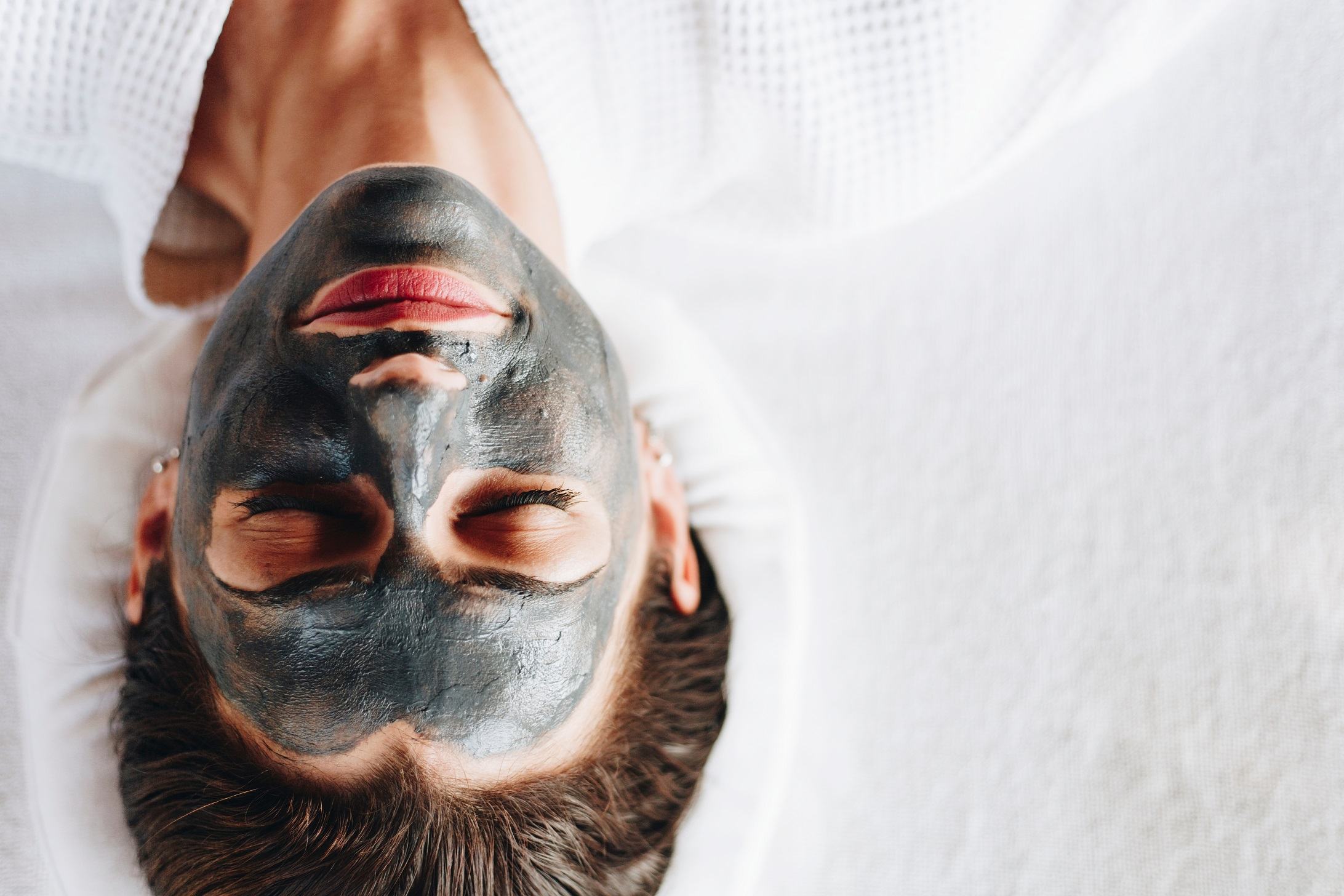 Woman relaxing with a charcoal facial mask.