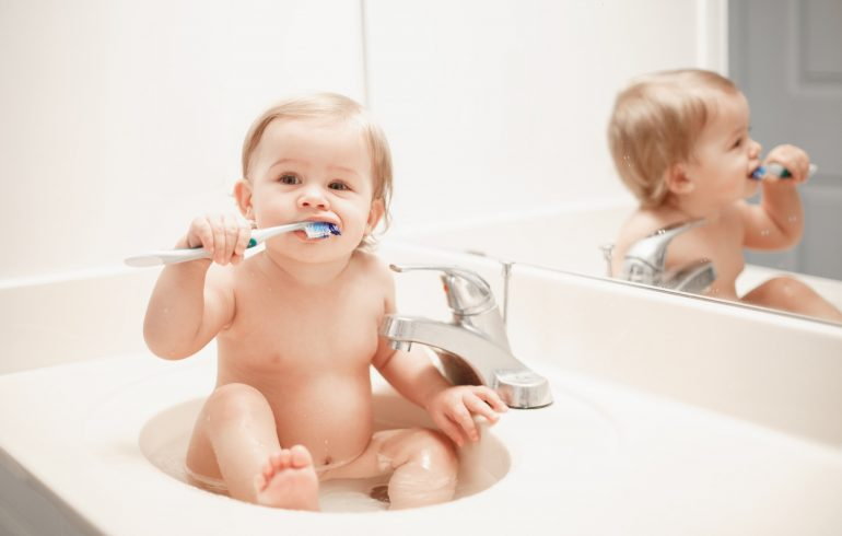 Baby brushing his teeth.