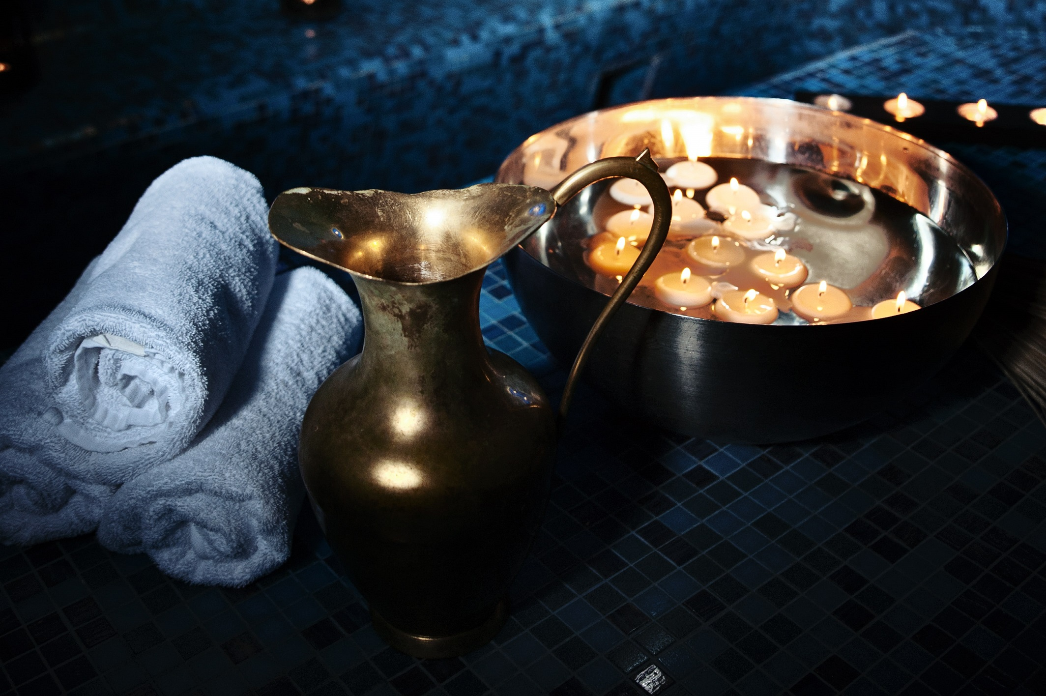 Candles in bowl, towels and jug in Hammam spa.